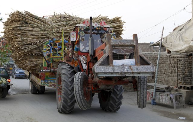The front wheels of a tractor, pulling a trailer overloaded with sugarcane, are seen lifted off the ground as it passes through the streets of Karor Lan Esan, Pakistan December 6, 2015. (Photo by Caren Firouz/Reuters)
