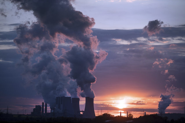 In this April 27, 2017 file photo smoke billows out of the chimneys of the Neurath lignite power plant in Neurath. Germany. World leaders affirmed their commitment Thursday, June 1, 2017 to combating climate change ahead of U.S. President Donald Trump's announcement on whether he would pull out of the Paris climate accord. Trump is expected to announce his decision on Thursday afternoon. (Photo by Federico Gambarini/DPA via AP Photo)