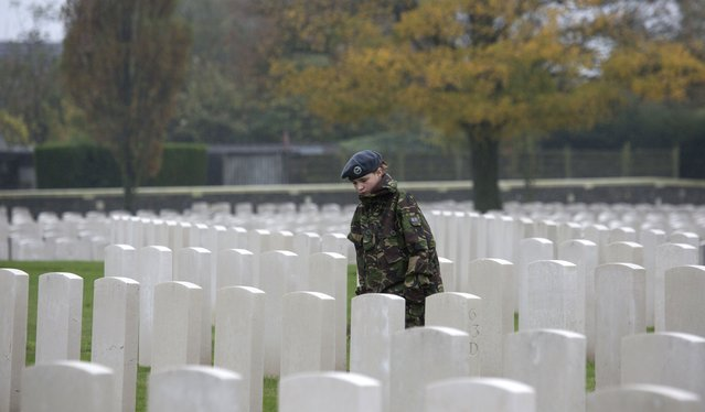 In this November 12, 2013, file photo, a young girl who is a member of the RAF cadets walks between gravestones at Tyne Cot World War One cemetery in Zonnebeke, Belgium. Tyne Cot is now the largest Commonwealth war cemetery in the world in terms of burials. There are 11,956 Commonwealth servicemen of the First World War buried or commemorated in the cemetery, 8,369 of those burials are unidentified. Other special memorials commemorate 20 casualties whose graves were destroyed by shell fire and there are 4 German burials, 3 being unidentified. (Photo by Virginia Mayo/AP Photo)