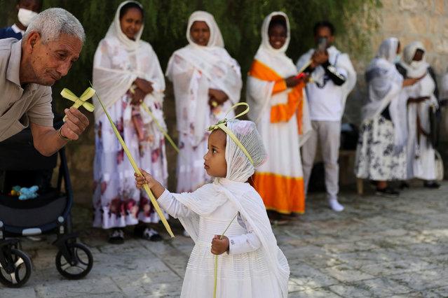 A man plays with a young girl as she holds a part of palm frond during an Orthodox Christian Palm Sunday procession, marking the start of Holy Week that ends on Easter Sunday, amid eased coronavirus (COVID-19) restrictions, at the Ethiopian section in the Church of the Holy Sepulchre in Jerusalem's Old City on April 25, 2021. (Photo by Ronen Zvulun/Reuters)