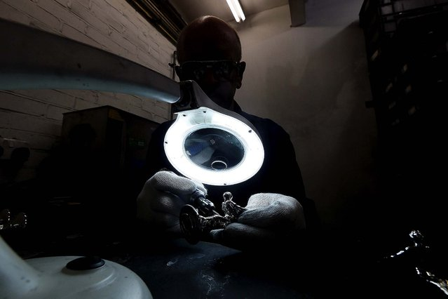 """Worker Ronald Little finishes a """"Spirit of Ecstasy"""". (Photo by Stefan Wermuth/Reuters)"""