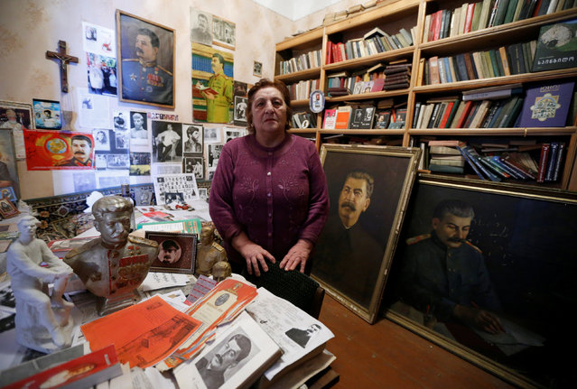 """Nazi Stefanishvili, a 73-year-old retired economist, poses for a portrait in a room dedicated to Stalin at her home in Gori, Georgia, December 6, 2016. """"Every morning I go to the room to say good morning to Stalin... I take part in every occasion marking the anniversary of his birthday or death"""", said Stefanishvili. """"I have paintings, a lot of books about Stalin, busts, old newspapers, souvenirs. Most I bought, others were gifts; some were even found in the garbage"""". (Photo by David Mdzinarishvili/Reuters)"""