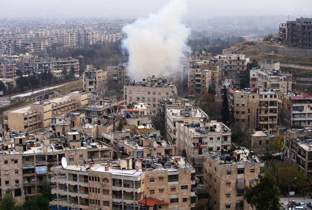 Smoke rises from the al-Ethaa government held neighbourhood in eastern Aleppo during clashes on December 5, 2016. The Syrian army has seized two-thirds of east Aleppo and continued to advance, pounding remaining opposition-held territory. (Photo by Youssef Karwashan/AFP Photo)