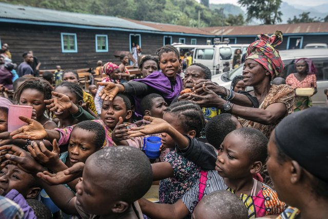 People who fled Goma, Congo, gather at a food distribution point Friday, May 28, 2021 in Sake, some 25 kms (16 miles) west of Goma where they found shelter following an official evacuation order five days after Mount Nyiragongo erupted. (Photo by Moses Sawasawa/AP Photo)