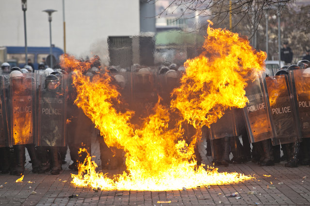 Supporters of the opposition throw molotov cocktail at Kosovo police forces guarding the government building in Kosovo capital Pristina on Saturday, January 9, 2016. A government building was set on fire in Pristina on Saturday as supporters of Kosovo's main opposition parties gathered during a rally organised as part of their continued attempts to bring down the government. Security forces used tear gas to push back protesters. (Photo by Visar Kryeziu/AP Photo)