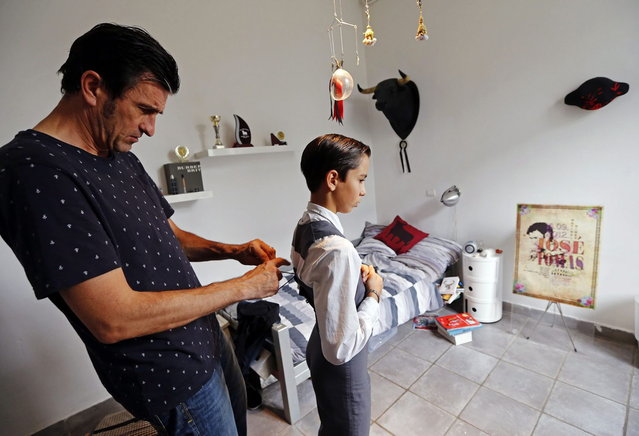Solal's father Christian helps his son Solal, a twelve-year-old toreador apprentice, get dressed before a beginner's bullfight (becerrada) in Nimes October 5, 2013. Since 1983, the French Tauromachy Centre in Nimes has trained some 1,000 youths in the art of bullfighting. Twenty of them have gone on to become professional matadors, facing fighting bulls in the arena. Twice a week, students take courses with a matador to learn the movements and gestures of the bullfighter in the ring, but without an animal present. Students train with calves in the surrounding fields during spring, and regularly participate in beginner's bullfights (becerradas) without killing calves. Solal has been taking courses for three years and Nino, for just a year now. Both are normally enrolled in French public schools, but have one thought in mind – bullfighting. They share a passion linked to the city of Nimes, famous for its ferias and bullring. (Photo by Jean-Paul Pelissier/Reuters)