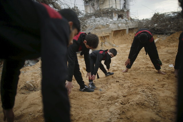 Palestinian youths and boys exercise they demonstrate their ninja-style skills for a photographer in front of the ruins of buildings, that were destroyed in the 2014 war, in the northern Gaza Strip January 29, 2016. (Photo by Mohammed Salem/Reuters)