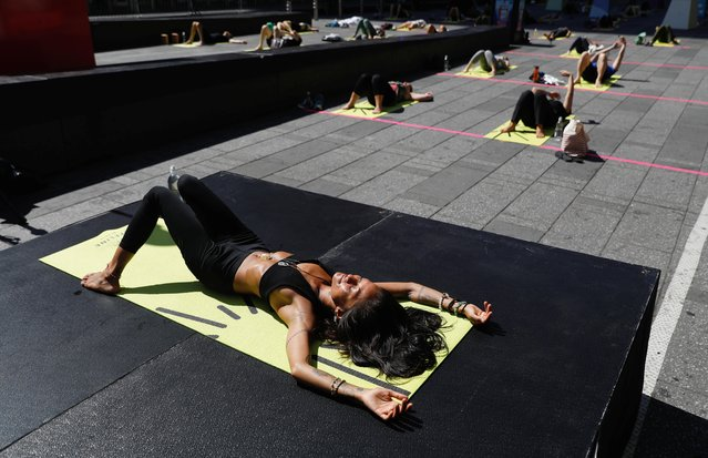 """People participate in the """"Solstice in Times Square: Mind Over Madness Yoga"""" to celebrate the summer solstice in New York, U.S. June 20, 2021. (Photo by Andrew Kelly/Reuters)"""