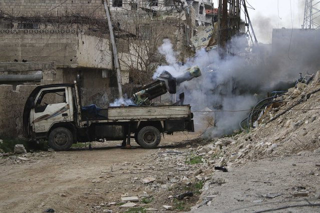 Rebel fighters from the Free Syrian Army's Al Rahman legion fire a locally-made weapon towards forces loyal to Syria's President Bashar al-Assad on the frontline, in the eastern Damascus suburb of Ghouta March 12, 2015. (Photo by Diaa Al-Din/Reuters)