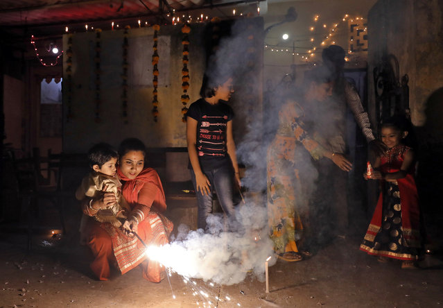 A woman holds a child in her lap as they light a sparkler to celebrate Diwali in New Delhi, India on November 7, 2018. (Photo by Anushree Fadnavis/Reuters)