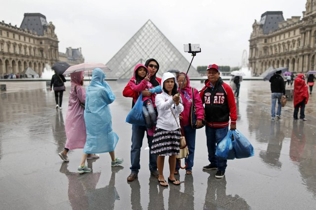 Tourists take a selfie near the Pyramid of the Louvre Museum on a rainy summer day in Paris, in this July 9, 2014 file photo. (Photo by Charles Platiau/Reuters)