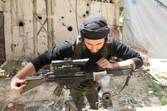 A Free Syrian Army fighter repairs a weapon at the Yarmouk Palestinian refugee camp April 29, 2015. (Photo by Ward Al-Keswani/Reuters)
