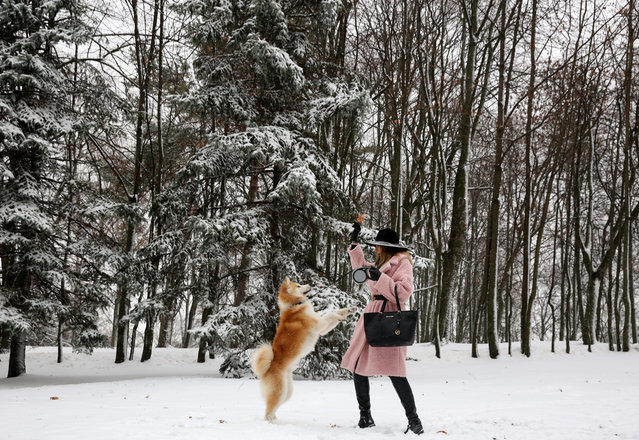 A woman plays with a dog in a Central Gorky Park on a winter day in Minsk, Belarus, 08 December 2018. Temperature in Minsk is zero degrees Celsius, local media reports. (Photo by Tatyana Zenkovich/EPA/EFE)