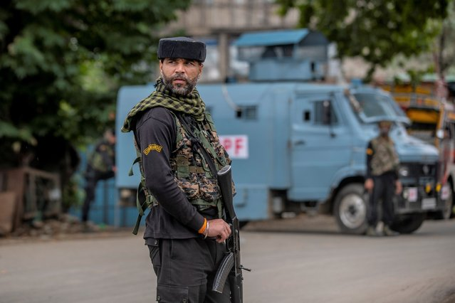 An Indian paramilitary soldier stands guard on a road leading towards the site of a gunfight in Pulwama, south of Srinagar, Indian controlled Kashmir, Wednesday, July 14, 2021. Three suspected rebels were killed in a gunfight in Indian-controlled Kashmir on Wednesday, officials said, as violence in the disputed region increased in recent weeks. Two residential houses were also destroyed. (Photo by Dar Yasin/AP Photo)