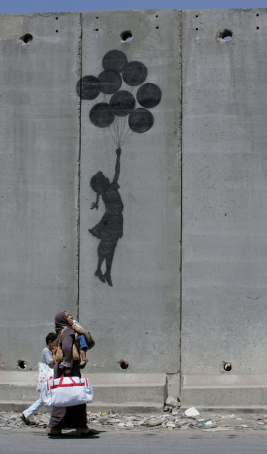 A Palestinian woman and her children walk past a Banksy drawing on the controversial Israeli barrier in the West Bank city of Aram in 2005. (Photo by Ammar Awad/Reuters)