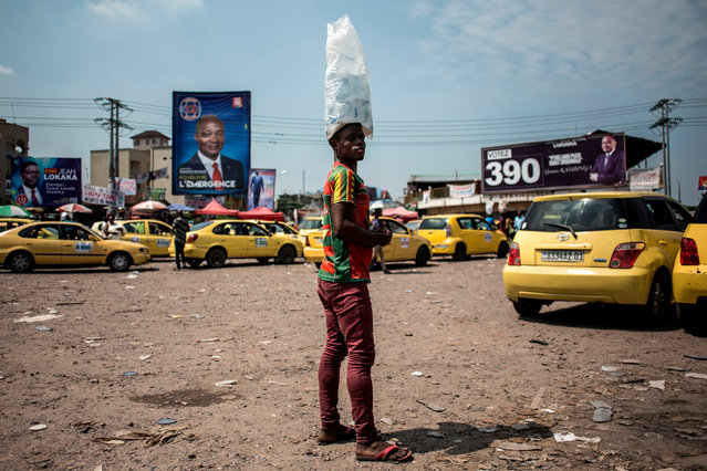 A man selling bags of water is seen at a taxi parking bay lined with campaign posters in the district of Lingwala in Kinshasa on December 18, 2018. Democratic Republic of Congo goes to the polls on December 23, 2018 in elections which could see the country emerge from 17 years of conflict-ridden rule under controversial President Joseph Kabila. (Photo by John Wessels/AFP Photo)