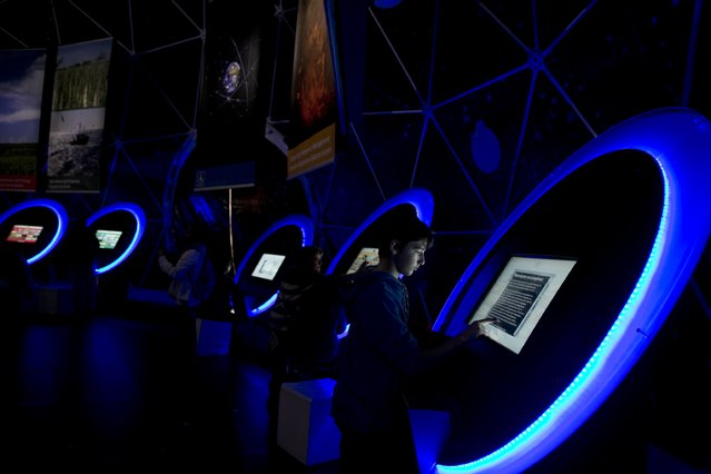 A young man touches a screen during the opening day of a European space exhibition, in central Athens, on Saturday, March 28, 2015. The exhibition shows how space and its applications provide benefits to Europe's citizens. (Photo by Petros Giannakouris/AP Photo)