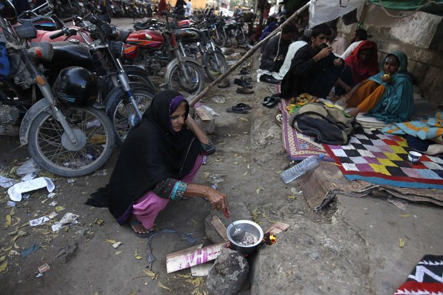 A woman, who lives with her family along a sidewalk, cooks near their makeshift home in Karachi February 16, 2015. (Photo by Akhtar Soomro/Reuters)
