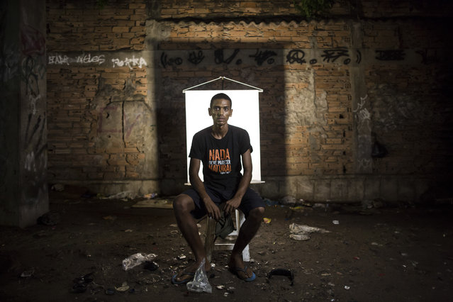 "In this March 17, 2015 photo, Anderson Pereira, 23, poses for a portrait in an open-air crack cocaine market, known as a ""cracolandia"" or crackland, where users can buy crack, and smoke it in plain sight, day or night, in Rio de Janeiro, Brazil. Pereira wears a T-shirt with a message that reads in Portuguese; ""Nothing should seem natural"". (Photo by Felipe Dana/AP Photo)"