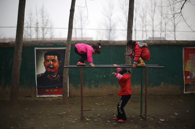 Students play next to a portrait of Soviet leader Joseph Stalin at the Democracy Elementary and Middle School in Sitong town, Henan province December 3, 2013. (Photo by Carlos Barria/Reuters)