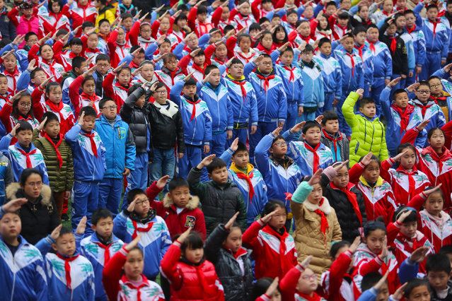 Schoolchildren salute during a flag raising ceremony on the first day of the new semester in Jiujiang, Jiangxi Province, China, February 19, 2016. (Photo by Reuters/Stringer)