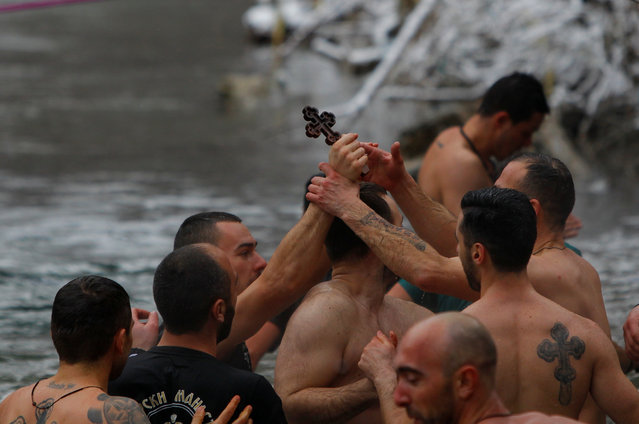 Men touch a cross during the Epiphany day celebration in Bitushe, Macedonia January 19, 2017. (Photo by Ognen Teofilovski/Reuters)