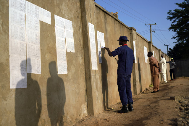 Nigerians check voters' lists at a polling station in Kaduna, Nigeria, Saturday, February 16, 2019. Nigeria's electoral commission delayed the presidential election until Feb. 23, making the announcement a mere five hours before polls were set to open. (Photo by Jerome Delay/AP Photo)