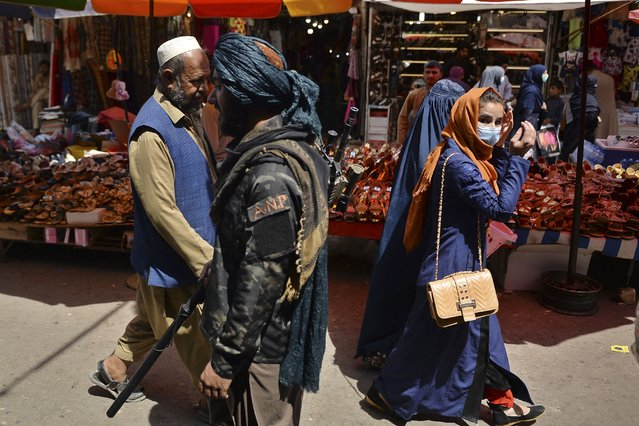 A Taliban fighter (C) walks past shoppers along Mandawi market in Kabul on September 1, 2021 a day after the US pulled all its troops out of the country to end a brutal 20-year war – one that started and ended with the hardline Islamist in power. (Photo by Hoshang Hashimi/AFP Photo)