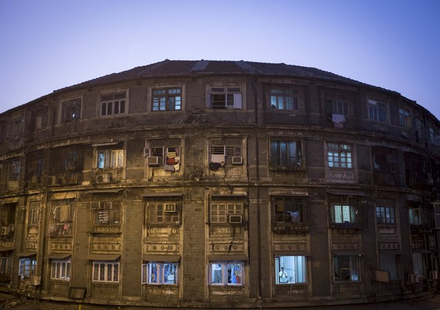 A man stands next to a window of a residential building in central Mumbai January 28, 2015.  The cost for buying a residential apartment in Mumbai close to the city centre ranges from 12,000 Indian rupees ($ 200) per square feet to 112,552 Indian rupees ($ 1800) per square feet. (Photo by Danish Siddiqui/Reuters)