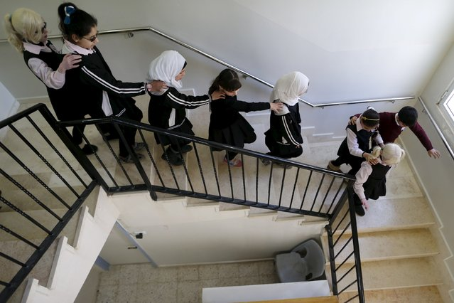 Blind and visually impaired Palestinian students walk down the stairs at a school, where they are taught English through song and music, at a school in the West Bank city of Hebron March 2, 2016. (Photo by Ammar Awad/Reuters)