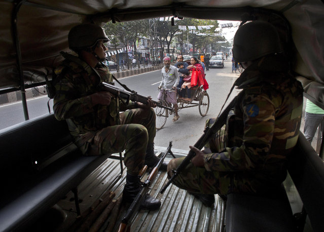 Bangladeshi army soldiers keep vigil as a rickshaw puller transports passengers on the eve of the general elections in Dhaka, Bangladesh, Saturday, December 29, 2018. As Bangladeshis get set for Sunday's parliamentary elections, there are fears that violence and intimidation could keep many away from the polls, including two opposition candidates who said police had barricaded them inside their homes. (Photo by Anupam Nath/AP Photo)