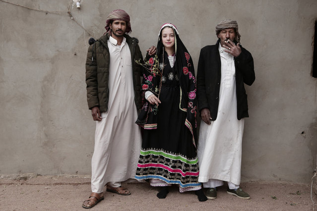 In this March 31, 2019 photo, an Egyptian student borrows a Bedouin wedding dress to pose for a photograph with Bedouin men from the Hamada tribe, in Wadi Sahw, Abu Zenima, in South Sinai, Egypt. Four Bedouin women are for the first time leading tours in Egypt's Sinai Peninsula, breaking new ground in their deeply conservative community, where women almost never work outside the home or interact with outsiders.  The tourists can only be women, and the tours can't go overnight. Each day before the sun sets, the group returns to the Hamada's home village in Wadi Sahu, a narrow desert valley. (Photo by Nariman El-Mofty/AP Photo)