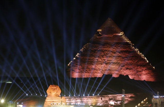 Lights illuminates the sky over the historical site of the Giza Pyramids and Sphinx to celebrate the African Cup of Nations draw in Cairo, Egypt, Friday, April 12, 2019. The tournament which will feature 24 teams will be held in Egypt in June 2019. (Photo by Amr Nabil/AP Photo)