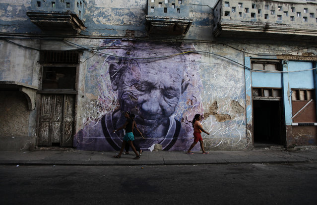 "People walk beside a creation by Cuban-American artist Jose Parla and JR on a street wall in Havana, May 9, 2012. The piece is part of the ""Wrinkles Of The City"" project, which combines JR's pictures of Cuban elderly people in the neighborhood with Parla's calligraphic messages. (Photo by Desmond Boylan/Reuters)"