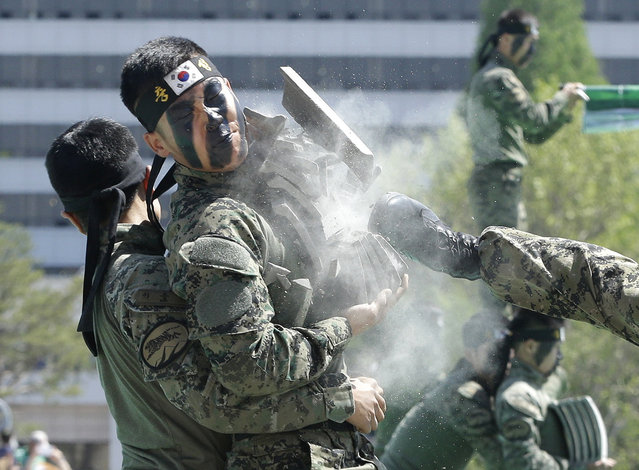 A soldier of the South Korean army special forces endures the pain as his fellow soldier breaks stone plates held by him by kicking during a martial arts demonstration for Children's Day at the War Museum in Seoul, Tuesday, May 5, 2015. May 5 is celebrated as Children's Day, a national holiday, in South Korea. (Photo by Ahn Young-joon/AP Photo)