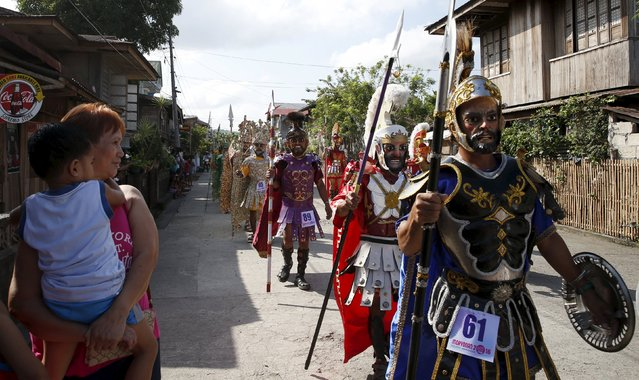 """Residents watch mask-wearing penitents locally called """"Morions"""", as they parade during the start of Holy Week celebrations in Mogpog, Marinduque in central Philippines March 21, 2016. The Moriones is an annual festival held on Holy Week on the island of Marinduque, Philippines. The """"Moriones"""" are men and women in costumes and masks replicating the garb of biblical Roman soldiers as interpreted by local folks. (Photo by Erik De Castro/Reuters)"""