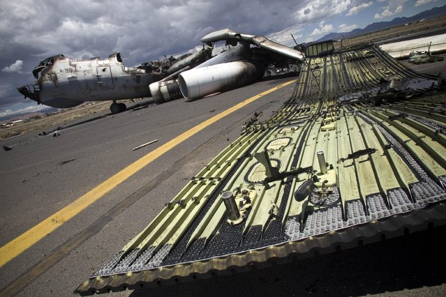 The wreckage of a military transport aircraft destroyed by Saudi-led airstrikes, at the Sanaa International airport, in Yemen, Tuesday, May 5, 2015. A Saudi-led coalition continues to bomb Shiite rebels also known as Houthis and allied forces across the country. The airstrikes campaign, which began on March 26, and the ground fighting have killed hundreds and displaced at least 300,000 Yemenis. (Photo by Hani Mohammed/AP Photo)