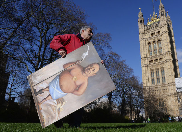 Satirical artist Kaya Mar carries one of his paintings depicting Scottish First Minister Alex Salmond with a petrol pump through Westminster, whilst both Prime Minister David Cameron's and Mr Salmond's held cabinet were holding separate meetings in Aberdeen, on February 24, 2014. (Photo by Stefan Rousseau/PA Wire)