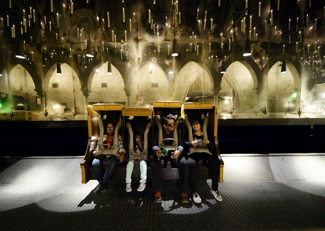 """Guests take a ride inside the Hogwarts School during a soft opening and media tour of """"The Wizarding World of Harry Potter"""" theme park at the Universal Studios Hollywood in Los Angeles, California in this picture taken March 22, 2016. (Photo by Kevork Djansezian/Reuters)"""