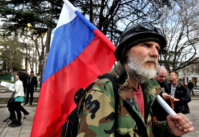 A Pro-Russian activist holds the Russian flag during a rally in Simferopol on March 6, 2014. Pro-Moscow authorities in Crimea today asked Russian President Vladimir Putin to examine a request for their region to join the Russian Federation, which will be put to a referendum on March 16. (Photo by Genya Savilov/AFP Photo)