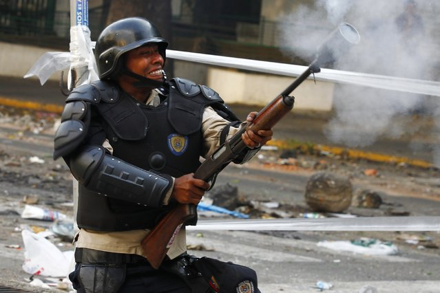 A riot policeman shoots tear gas at anti-government protesters during a protest in Caracas March 8, 2014. Latin American foreign ministers will meet next week to discuss the unrest in Venezuela that has left at least 20 dead and convulsed the South American OPEC nation, diplomatic sources said on Friday. (Photo by Carlos Garcia Rawlins/Reuters)