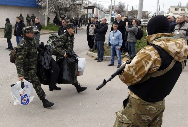 Ukrainian servicemen carry their belongings as they pass by an armed man while leaving the territory of the naval headquarters in Sevastopol, March 19, 2014. (Photo by Vasily Fedosenko/Reuters)