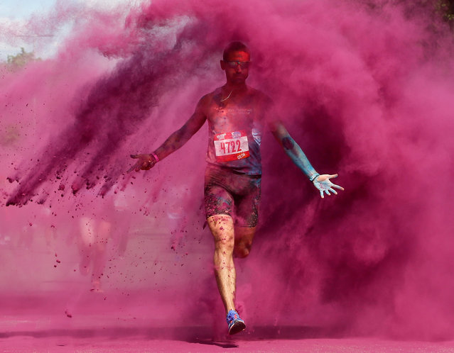 A participant runs through coloured powder during the Colour Run race in Moscow, Russia on June 2, 2019. (Photo by Evgenia Novozhenina/Reuters)