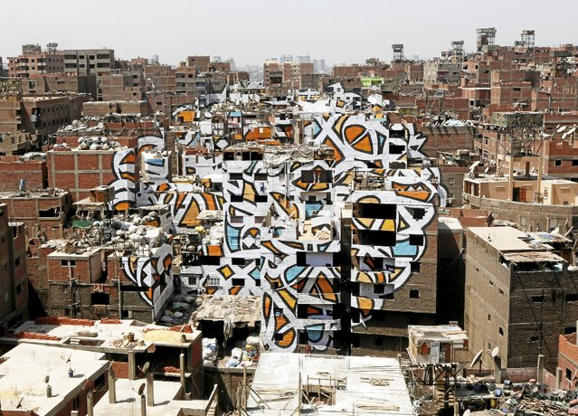 """A mural painted on the walls of houses in Zaraeeb, created by French-Tunisian artist El Seed, is pictured in the shanty area known also as Zabaleen or """"Garbage City"""" on the Mokattam Hills in eastern Cairo, Egypt, April 4, 2016. (Photo by Amr Abdallah Dalsh/Reuters)"""