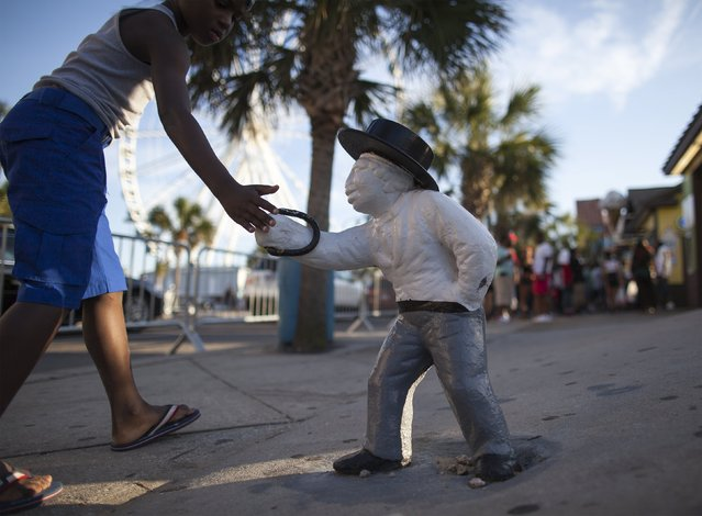 A boy touches an old lawn jockey that has been painted white on Ocean Boulevard during the 2015 Atlantic Beach Memorial Day BikeFest in Myrtle Beach, South Carolina May 24, 2015. (Photo by Randall Hill/Reuters)