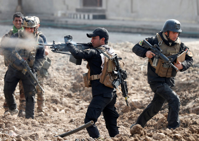 An Iraqi special forces soldier fires as other soldiers runs across a street during a battle in Mosul, Iraq March 1, 2017. (Photo by Goran Tomasevic/Reuters)