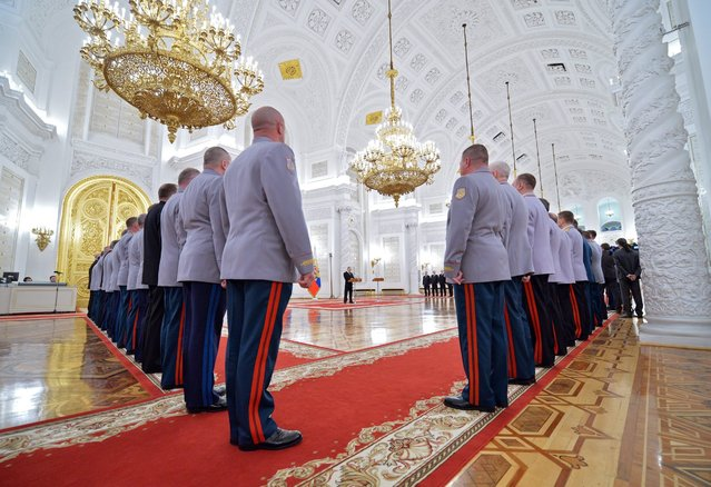 Russian President Vladimir Putin (back, C) speaks during a ceremony to present newly appointed to senior command posts officers  at the St George Hall in the Grand Kremlin Palace in Moscow, Russia, 21 April 2016. (Photo by Alexei Druzhinin/EPA/Sputnik/Kremlin)