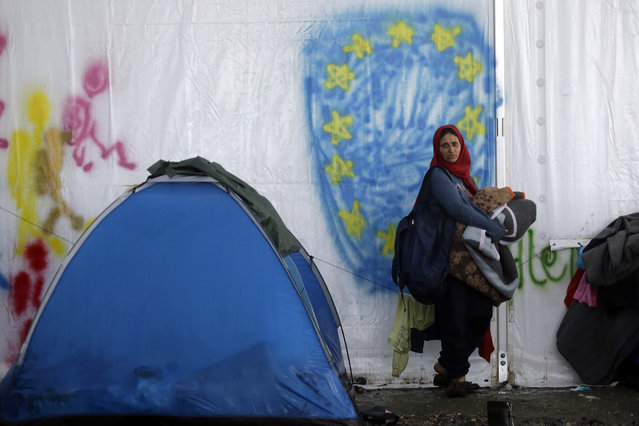 A woman standing in front of a graffiti depicting the EU flag, holds her blankets at the end of a rainstorm at the northern Greek border point of Idomeni, Greece, Sunday, April 24, 2016. Many thousands of migrants remain at the Greek border with Macedonia, hoping that the border crossing will reopen, allowing them to move north into central Europe. (Photo by Gregorio Borgia/AP Photo)