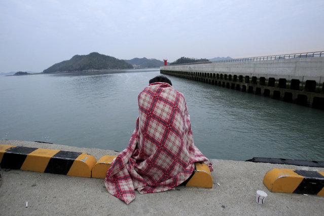 A relative waits for their missing loved one at a port in Jindo, South Korea, Wednesday, April 16, 2014. A ferry carrying 459 people, mostly high school students on an overnight trip to a tourist island, sank off South Korea's southern coast on Wednesday, leaving nearly 300 people missing despite a frantic, hours-long rescue by dozens of ships and helicopters. (Photo by Ahn Young-joon/AP Photo)