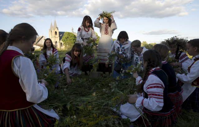 Belarusian women and girls make wreaths as they take part in the Ivan Kupala festival near the town of Rakov, west of Minsk June 27, 2015. (Photo by Vasily Fedosenko/Reuters)